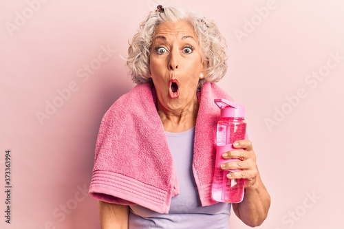 Photo Senior grey-haired woman wearing sportswear and towel drinking bottle of water s