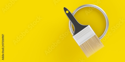 Photo Paintbrush on top of silver paint bucket with yellow paint on yellow background,
