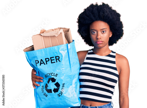 Young african american woman holding recycling bag with paper and cardboard thin Wallpaper Mural