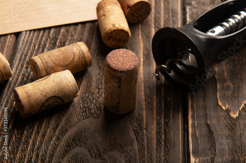 Fototapeta Wine corks and corkscrew on wooden table