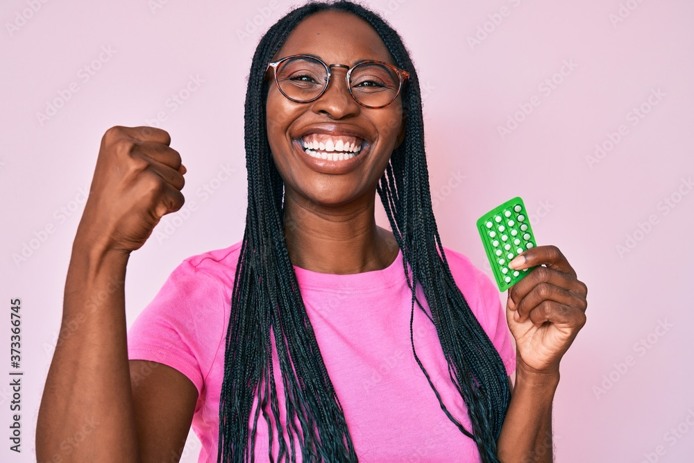 Fototapeta African american woman with braids holding birth control pills screaming proud, celebrating victory and success very excited with raised arms