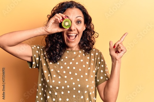 Middle age beautiful woman holding kiwi over eye smiling happy pointing with han Canvas