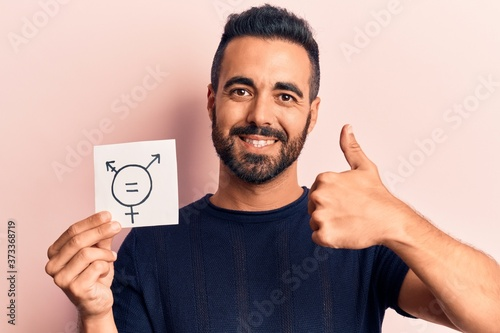 Cuadros en Lienzo Young hispanic man holding transgender symbol reminder smiling happy and positiv
