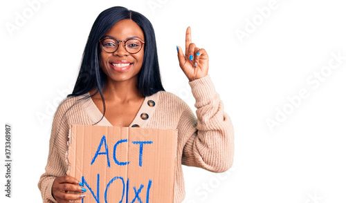 Young african american woman holding act now banner surprised with an idea or qu Fotobehang