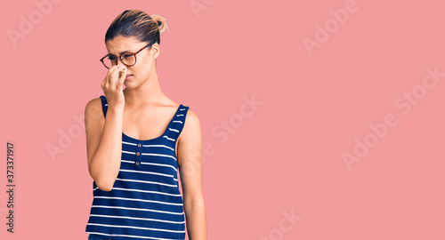 Foto Young beautiful woman wearing casual clothes and glasses smelling something stinky and disgusting, intolerable smell, holding breath with fingers on nose