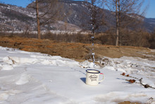 Drops Of Clean Drinking Water From Lake Baikal Are Splashed From A Metal Aluminum Mug On The Snow On A Picturesque Mountain Background On A Clear Winter Day Among Coniferous Trees.