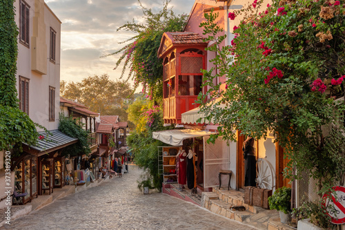 Fotografie, Obraz Beautiful street in the Kas old town with boutique shops at sunset, Turkey