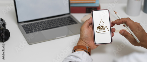 Close up view of male entrepreneur using mock up smartphone on worktable Canvas Print
