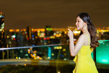 Woman In Evening Dress Holding Cocktail Over Night City Background