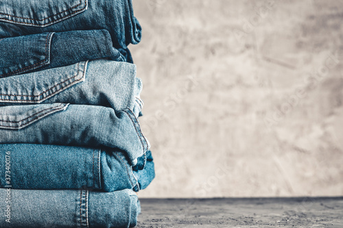 Stack of blue jeans on a gray background Fototapeta