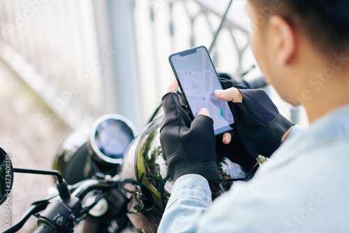 Fotomural Motorcyclist in fingerless gloves checking map on smartphone screen before ridin