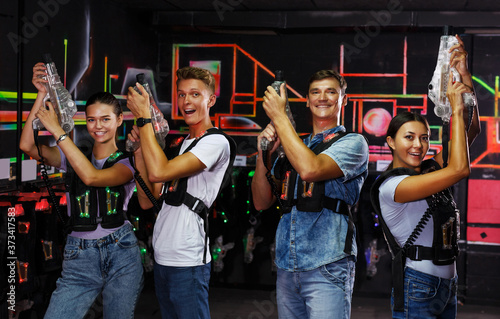 Group portrait of happy people with laser guns having fun together in dark labyr Fototapet
