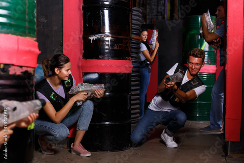 Portrait of happy young friends playing laser tag game with laser guns in dark room Poster Mural XXL