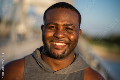 Obraz Portrait of young cheerful african-american man in sports clothing who is looking at camera and smiling. - fototapety do salonu