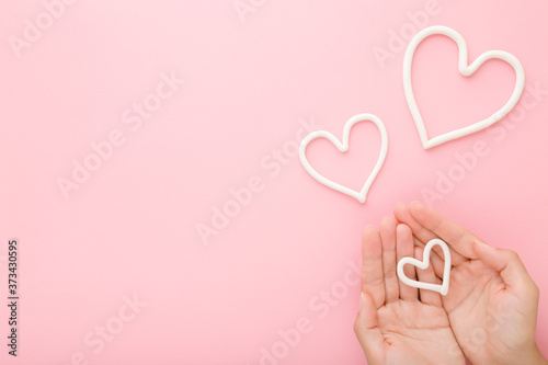 Photo Young woman palms and white heart shapes on pink table background