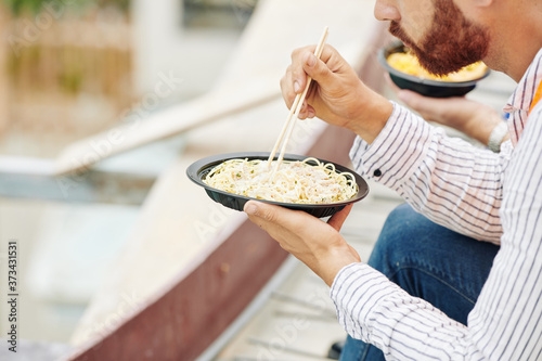 Obraz na plátně Cropped image of construction worker eating delicious noodles with shrimps he or