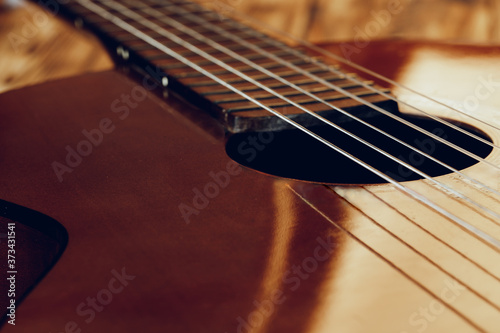 Wooden acoustic guitar body and fingerboard close up