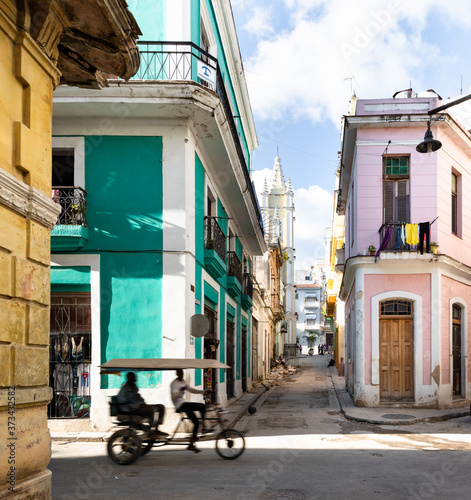 Fototapeta Road in old Havana with green car in front of colorful buildings with rickshaw