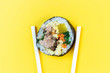 canvas print picture - Korean rolls gimbap wooden sticks on yellow background close-up.