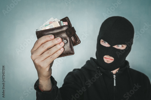 Photo Young ill-intended man wearing black mask holds the black leather men purse and looks to his loot