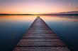 Leinwanddruck Bild - Old wooden pier at sunset. Long exposure, linear perspective
