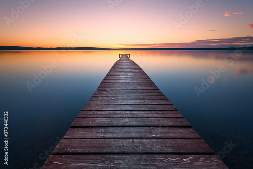 Fototapeta Old wooden pier at sunset. Long exposure, linear perspective