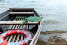 A Lifeboat Moored Near A Wooden Pier. Inside Is A Wooden Oar And A Life Preserver. Poor Working Conditions.