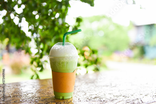 Green tea smoothie - Matcha green tea with milk on plastic glass on the wooden t Fototapete