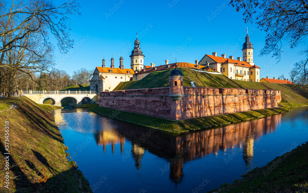 Fototapeta View of historic fortified Nesvizh Castle, landscape park and ponds on sunny winter day, Belarus