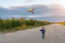 A Boy, A Child Runs Along The Road With A Flying Kite. I'm Learning To Fly A Kite. The Child Has A Happy, Fun, Carefree Childhood. Horizontal Photo.
