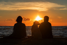 Family And Their Dog Watching Sunset On The Beach