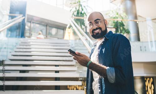 Fototapeta Half length portrait of cheerful male user with modern smartphone gadget in hand