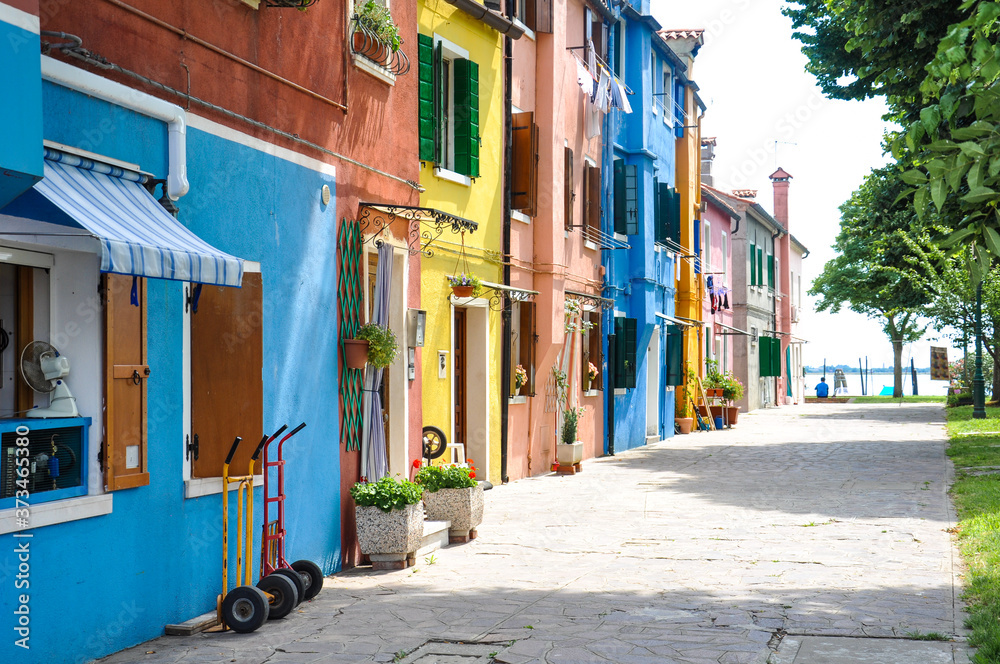Fototapeta View of a narrow street in Burano in Italy. Beautiful colorful houses in sunny weather.