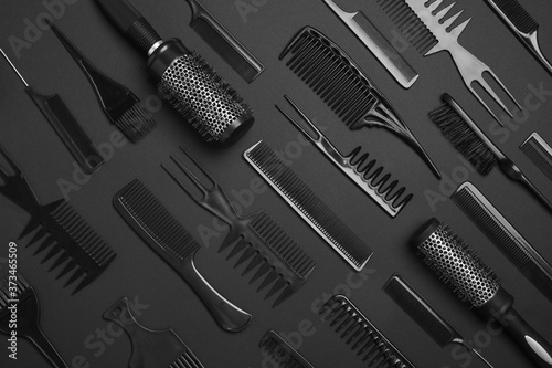 Flat lay composition with modern hair combs and brushes on black background