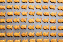 Delicious Goldfish Crackers On Grey Table, Flat Lay