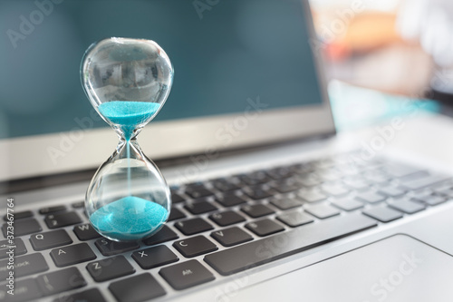 Obraz Hourglass on laptop computer concept for time management - fototapety do salonu