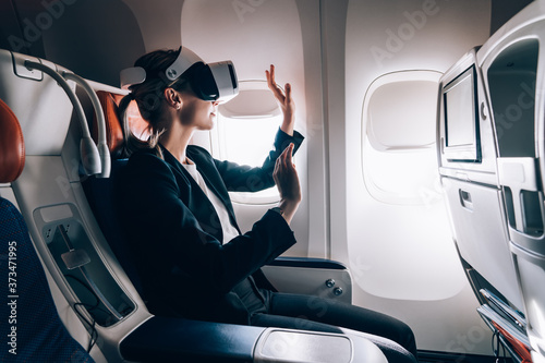 Amazed woman using glasses of virtual reality during flight Canvas
