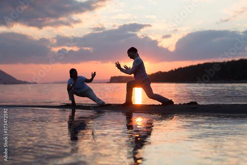 Obraz na plátně Man and woman doing Tai Chi chuan at sunset on the beach