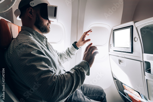 Photo Millennial male airplane passenger playing 3d game during jetliner flight testin