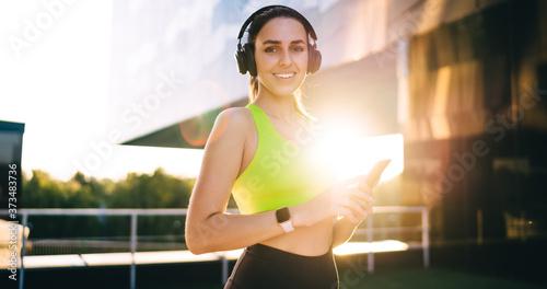 Fototapeta Half length of happy female athlete with cellular gadget enjoying free time for