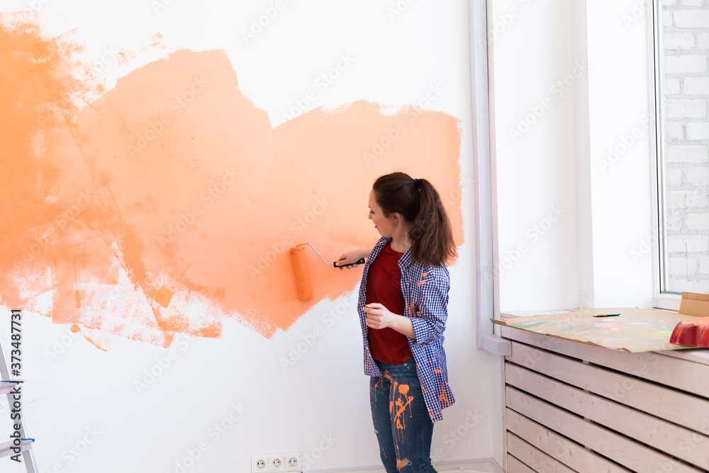 Fototapeta Lovely woman painting wall. Renovation, redecoration and repair concept.