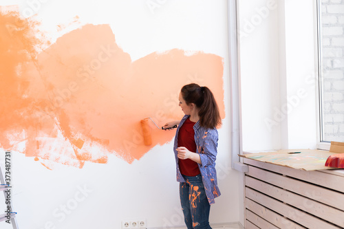 Fototapeta Lovely woman painting wall. Renovation, redecoration and repair concept. obraz