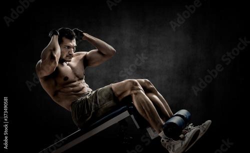 Fotografia man bodybuilder perform exercise on prelum abdominale on bench