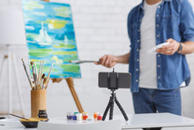 Painting Lesson Online. Guy Painting Landscape On Easel, On Table Are Glass With Brushes And Telephone