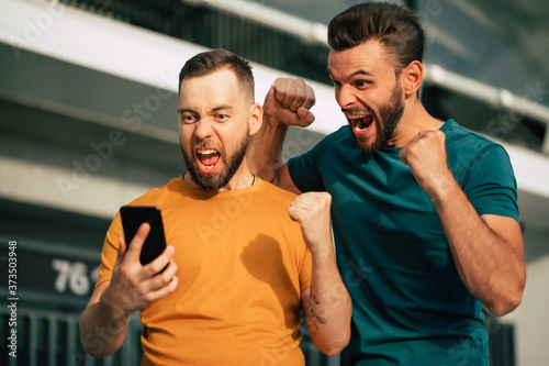 Obraz na plátně Two happy excited fan friends in euphoria mood after winning in a bet with a sma