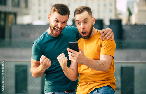 Canvas-taulu Two happy excited fan friends in euphoria mood after winning in a bet with a sma
