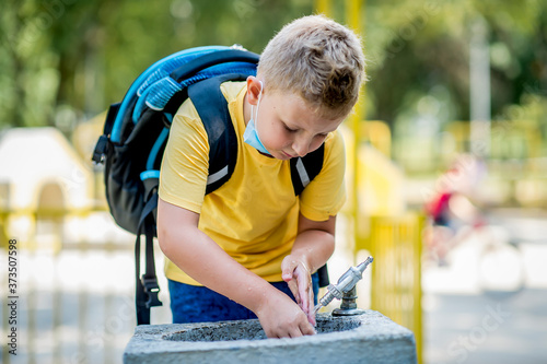 Boy  drinking water from a water fountain in a park Fototapete