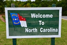 Wooden Green Signpost Of North Carolina, USA, White Letters, Welcome Greetings, Blue Flag