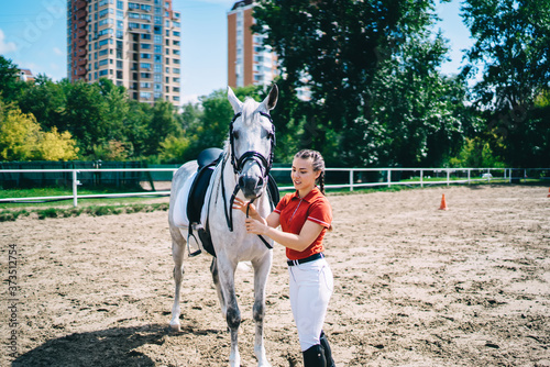 Photo Young horsewoman holding harness of white horse