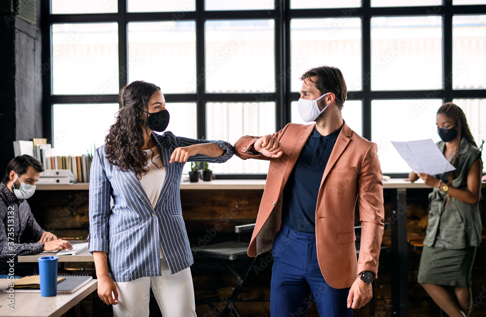Fototapeta Young businesspeople with face masks working indoors in office, greeting.